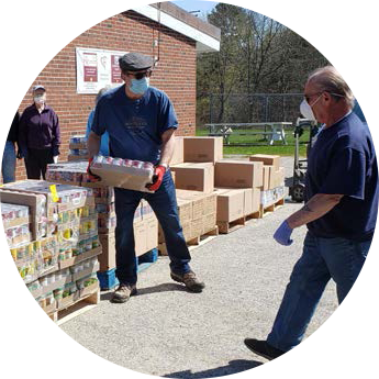 Photo of two individuals moving donations off of a pallet.